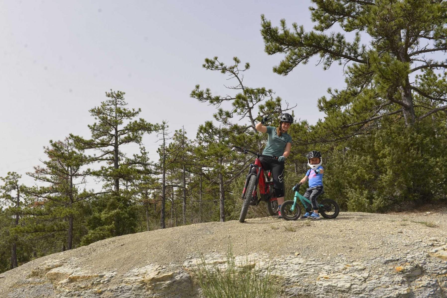 faire du vélo avec son enfant. Maman et enfant font coucou