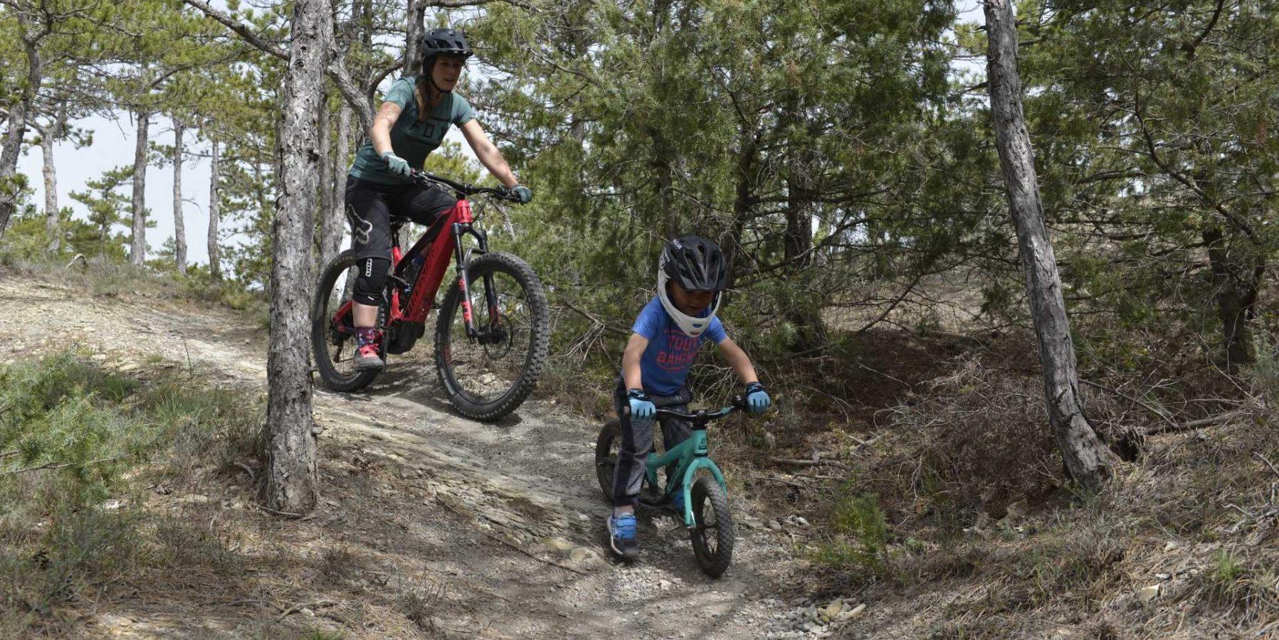 faire du vélo avec son enfant. Maman et enfant VTT descente